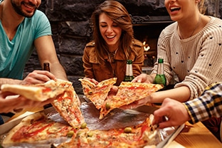 photo of friends eating pizza